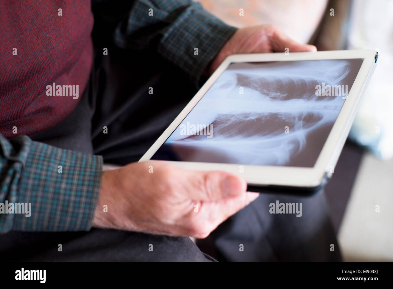 closeup of an old caucasian man observing a chest radiograph in a tablet, sitting in a couch - Stock Image