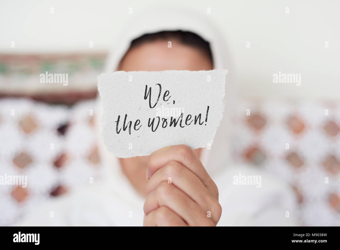 closeup of a young woman indoors wearing a white hijab showing a piece of paper in front of her face with the text - Stock Image
