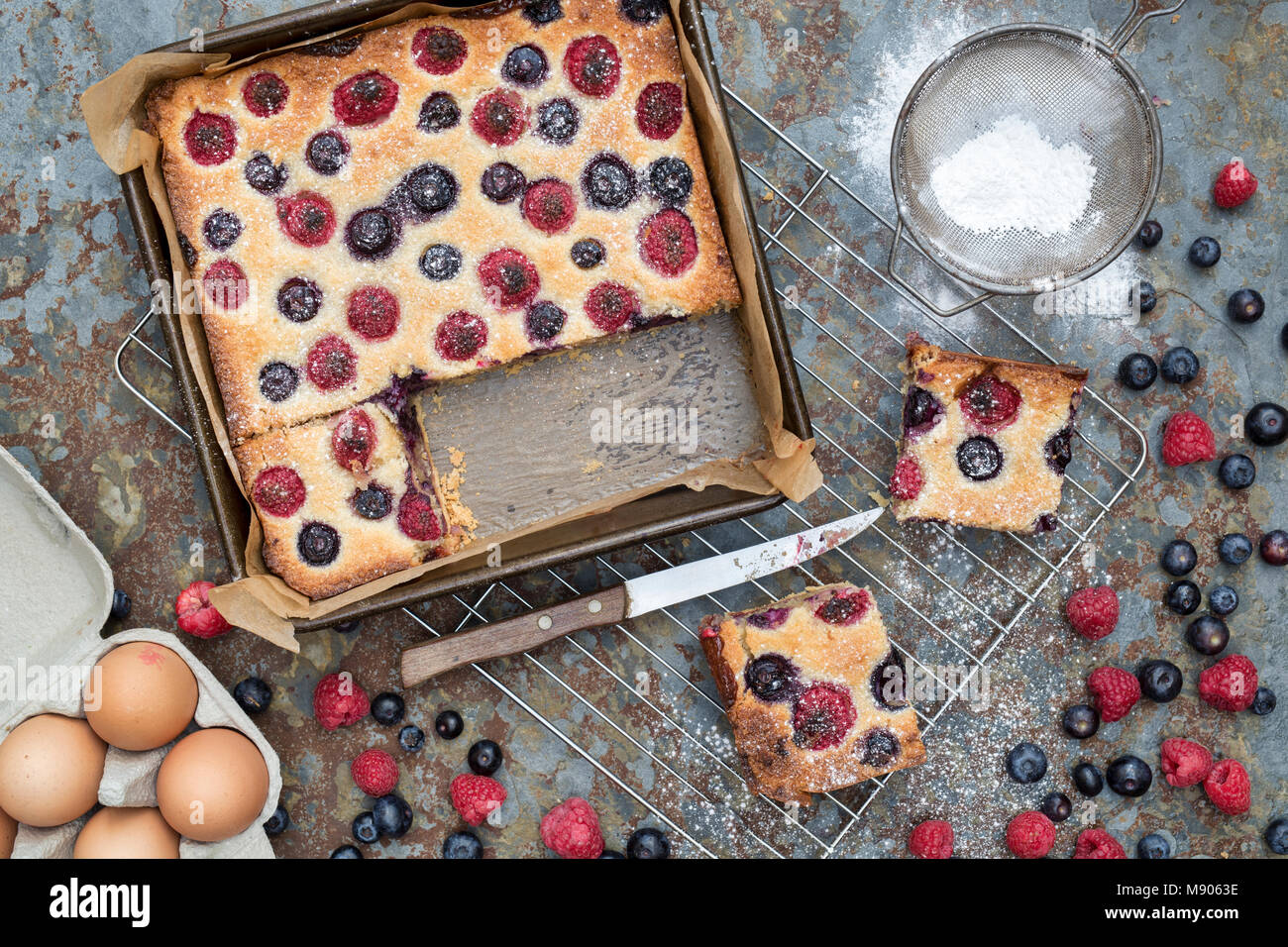 Homemade raspberry and blueberry frangipane tart with ingredients on a slate background - Stock Image