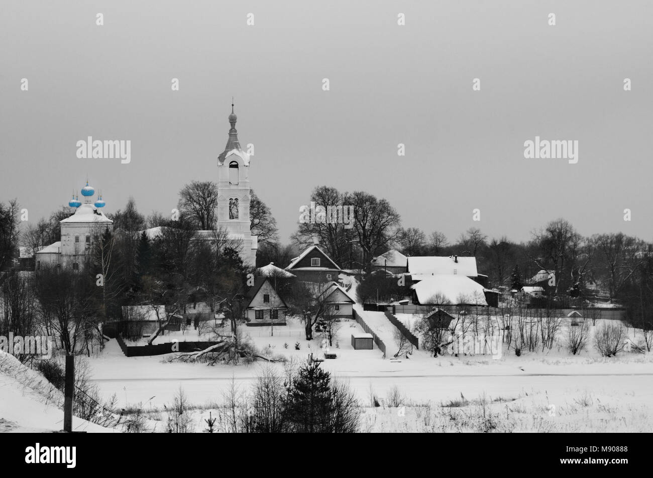 View over a small river on a village with church covered with snow on a gloomy winter day, Porechye village, Nerl - Stock Image