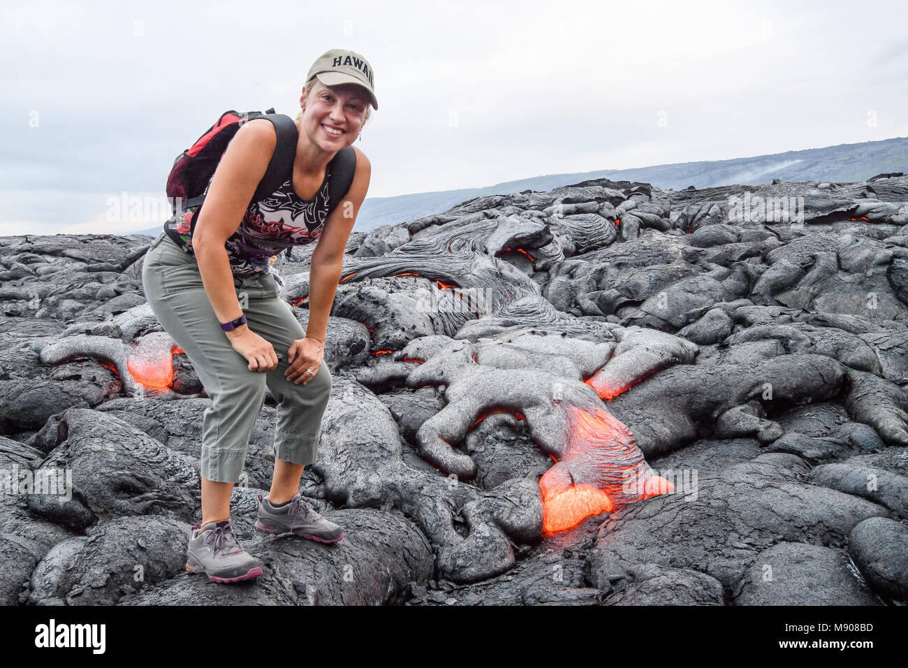 Tourist standing by lava flows at Kilauea volcano - Stock Image