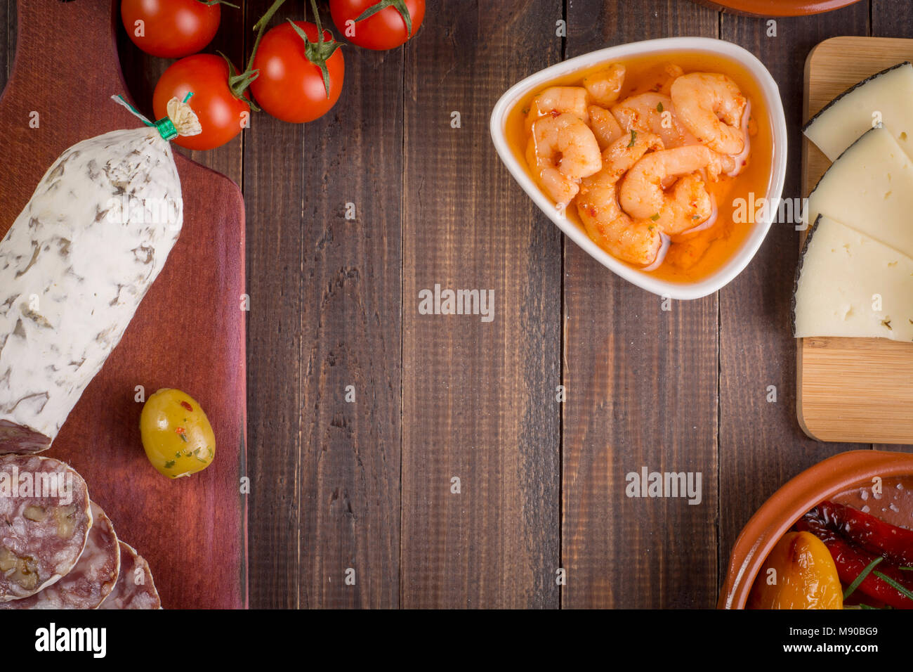 Mixed tapas food starters on table. Salami with walnuts, shrimps and manchego cheese. Top view. Copy space. - Stock Image