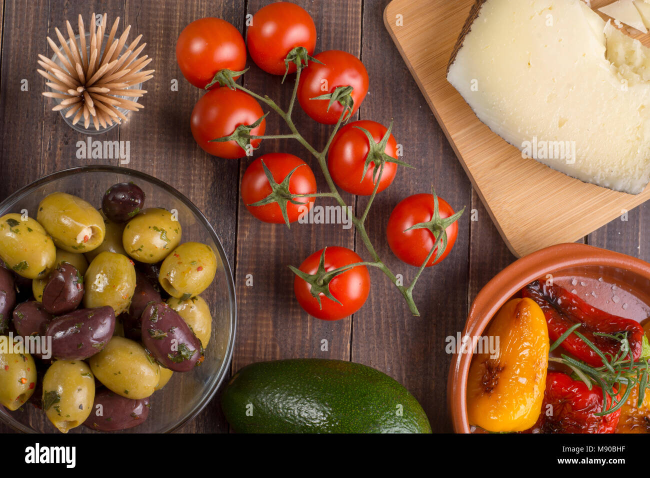 Mixed spanish tapas starters on table. Manchego cheese, olives and grilled pepper. Top view - Stock Image