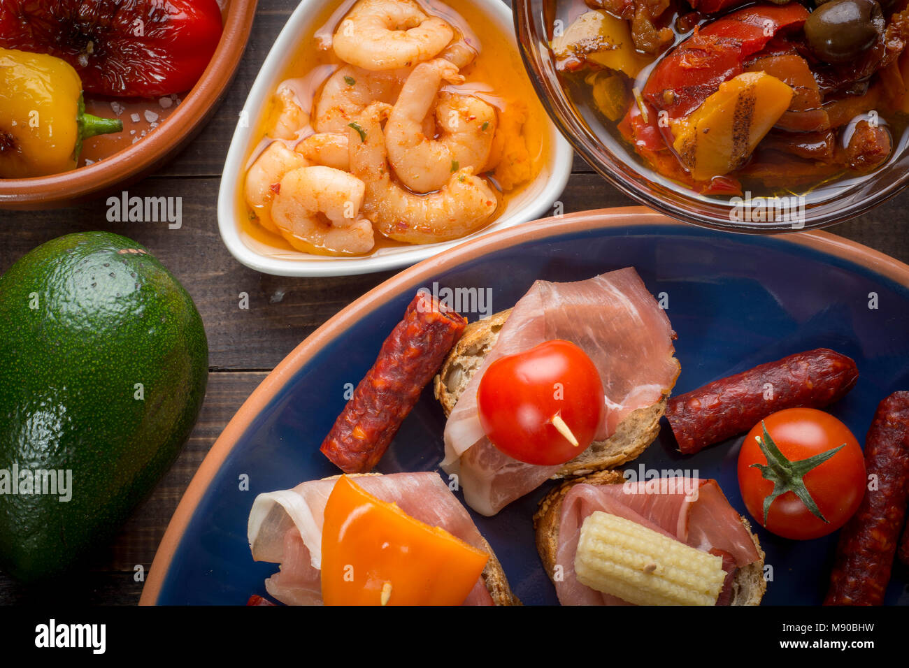 Mixed spanish tapas starters on table. Open sandwiches, shrimps, pickled vegetables. Top view - Stock Image