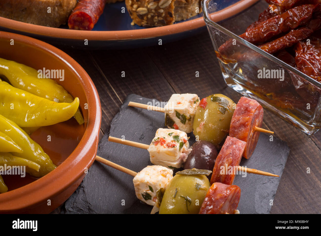 Small appetizers on skewer with cheese, olives and sausage. Tapas or antipasto - Stock Image