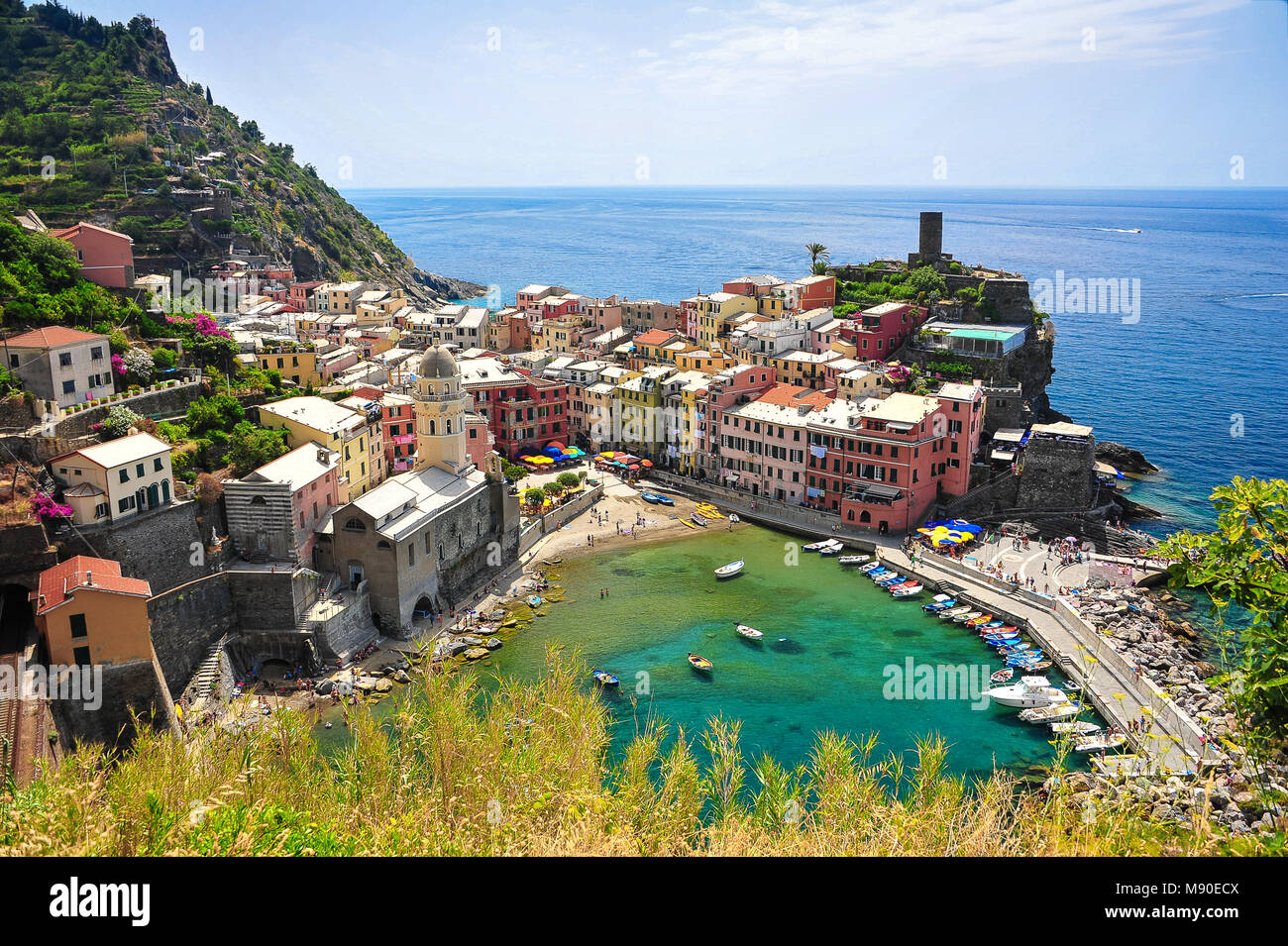 Prettily painted houses surrounded by an azure sea. Aerial view of Vernazza - one of five picturesque villages in - Stock Image