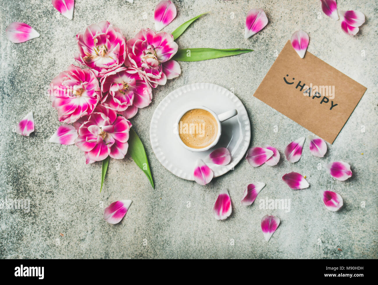 Cup of coffee surrounded with pink tulip flowers, marble background - Stock Image