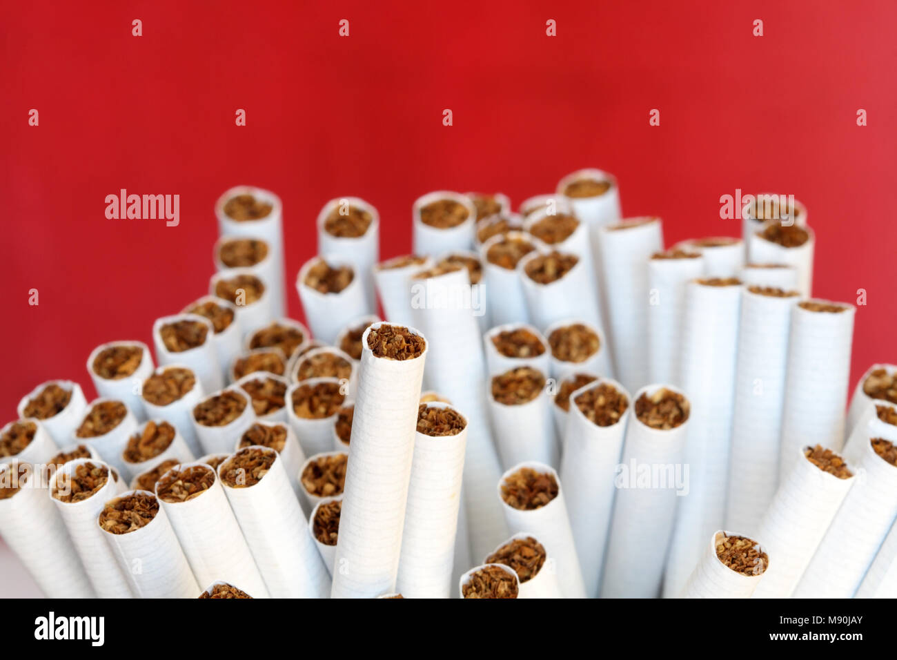 A lot of cigarettes on red background - Stock Image