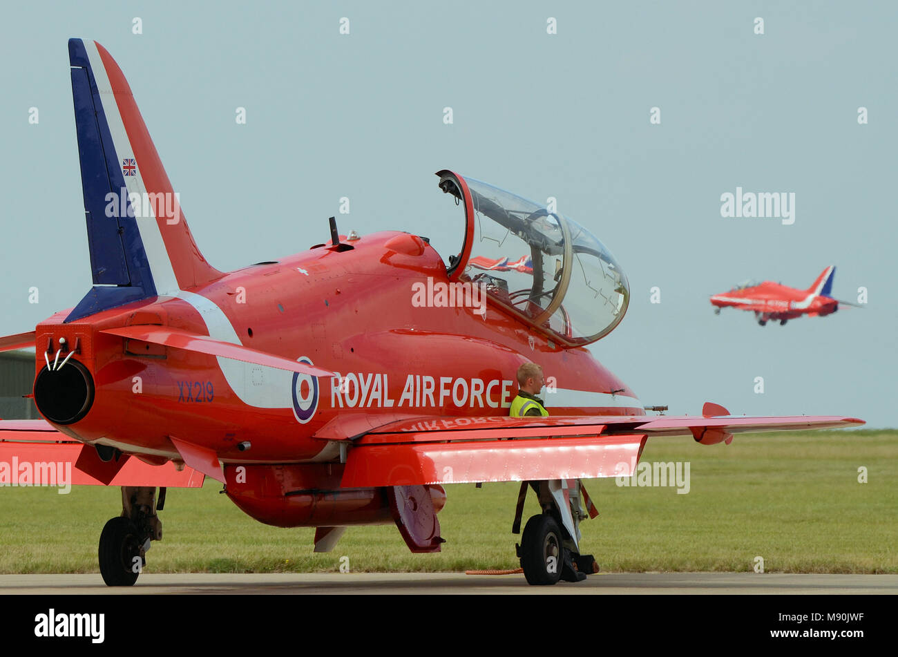Engineer mechanic watching jets of the Royal Air Force Red Arrows take off at RAF Scampton with spare jet. Space for copy - Stock Image