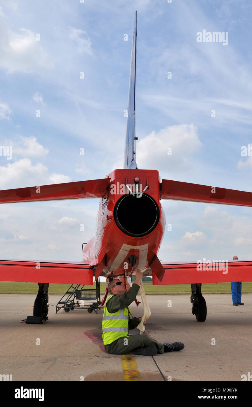 Engineer mechanic working on a Royal Air Force Red Arrows BAe Hawk T1 jet plane at RAF Scampton. Working. Servicing. Exhaust pipe. Jet pipe. Airplane - Stock Image