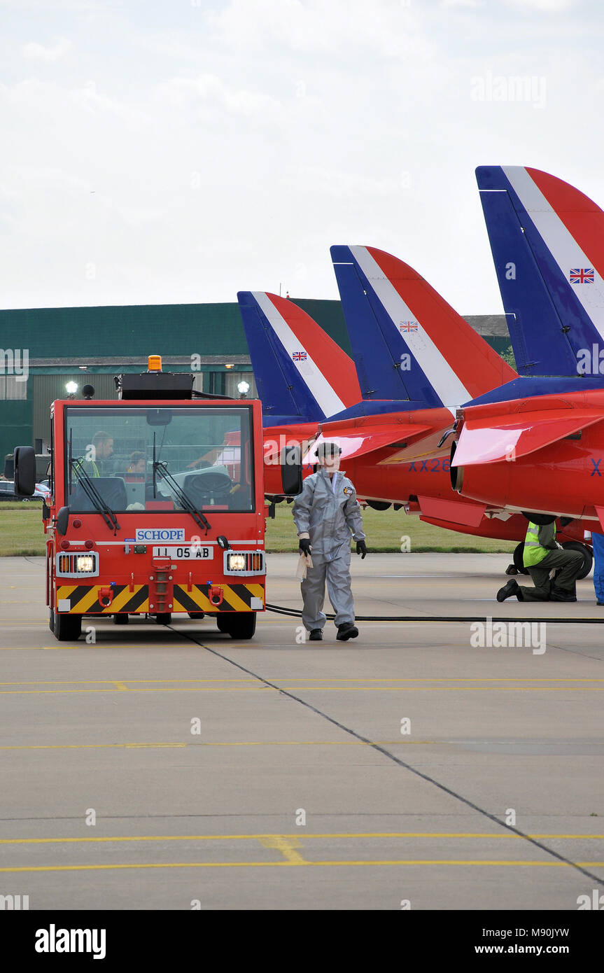 Royal Air Force Red Arrows engineer and smoke dye support team mechanics at RAF Scampton. Tug vehicle. BAe Hawk T1 plane tails. Row. Lined up - Stock Image