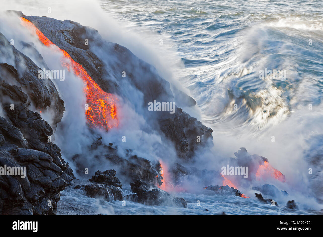 Sea water and molten rock splatter together as a wave crashes onto the Pahoehoe lava flowing from Kilauea into the Pacific Ocean near Kalapana, Big Is - Stock Image