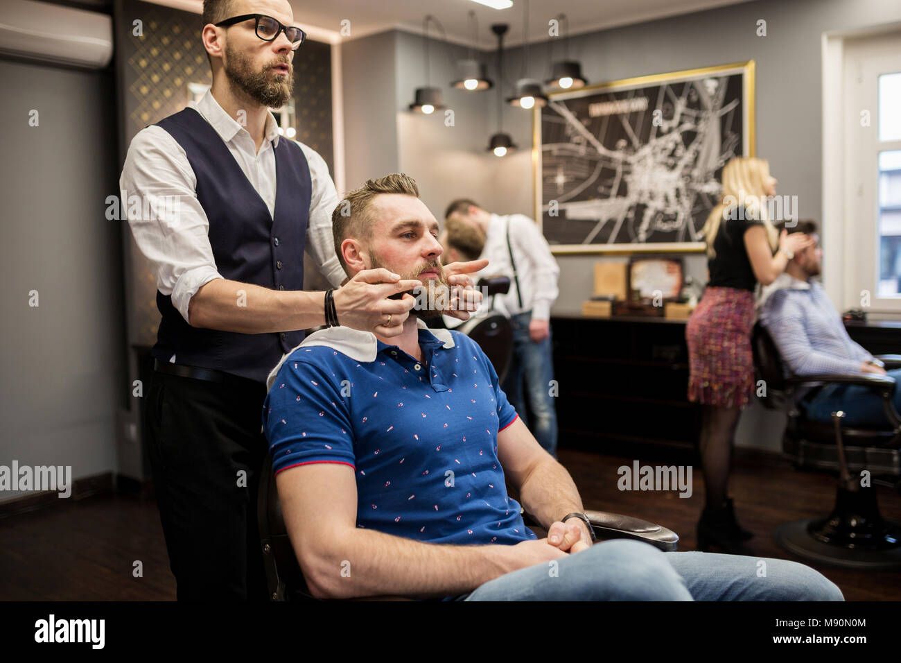 Portrait of barber preparing customer for shaving - Stock Image