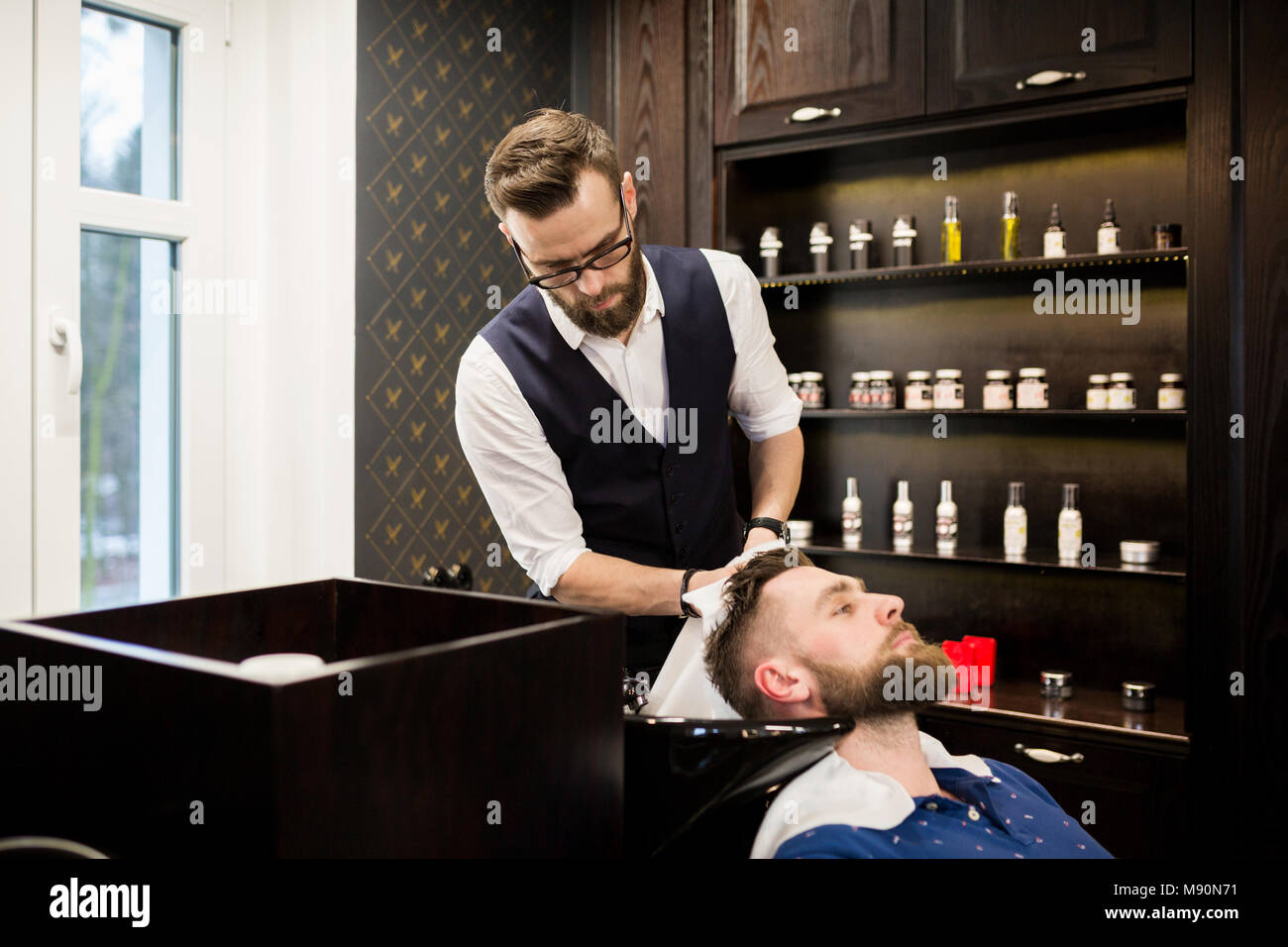 Portrait of young barber wiping customer hair with towel - Stock Image