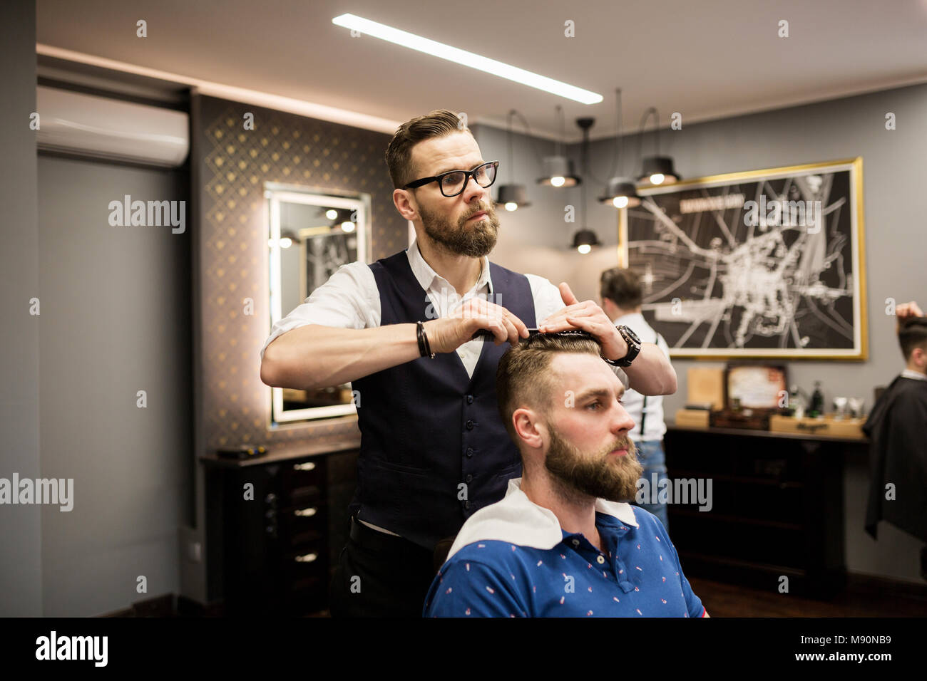 Portrait of hairdresser combing customer hair - Stock Image