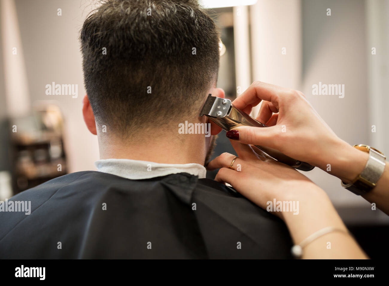 Cropped portrait of hairdresser hands trimming customer - Stock Image