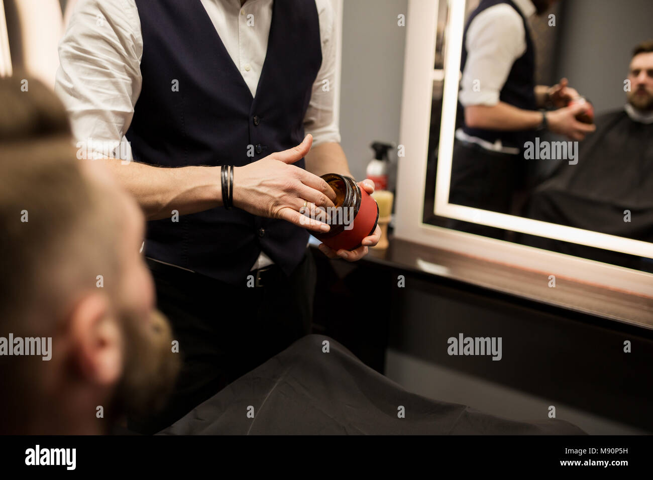 Cropped portrait of barber holding hair gel pack - Stock Image