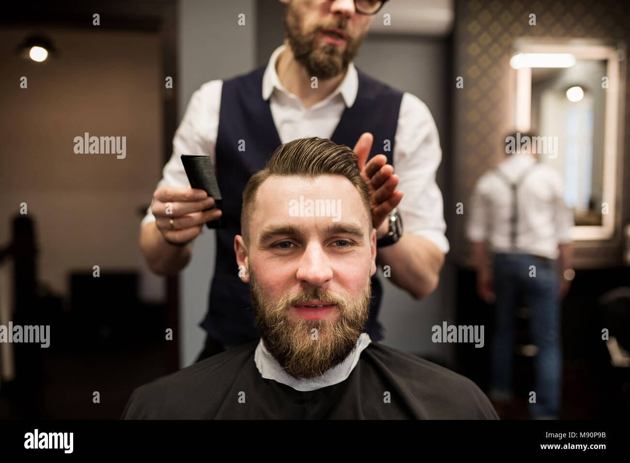 Front portrait of glad young man having hair cut at barber salon - Stock Image