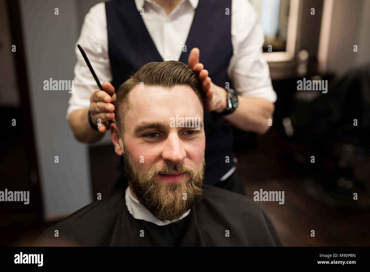 Portrait of happy man having hair cut at barber salon - Stock Image