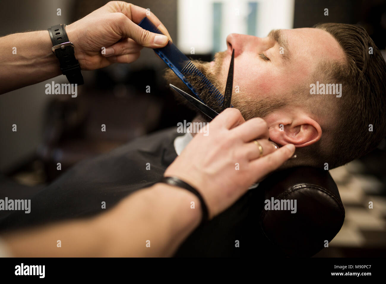 Profile portrait of young man having beard trimmed at barber salon - Stock Image