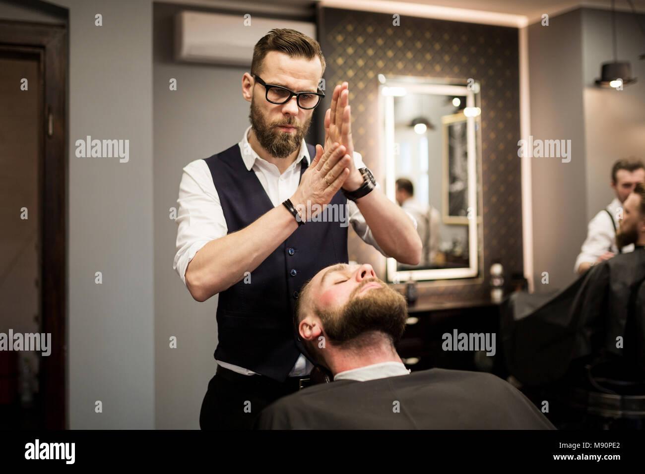 Portrait of barber rubbing foam in hands before shaving - Stock Image