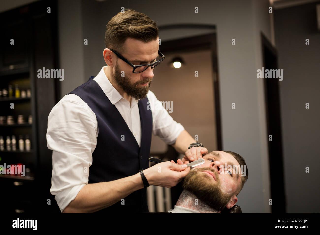 Portrait of barber shaving customer with razor - Stock Image