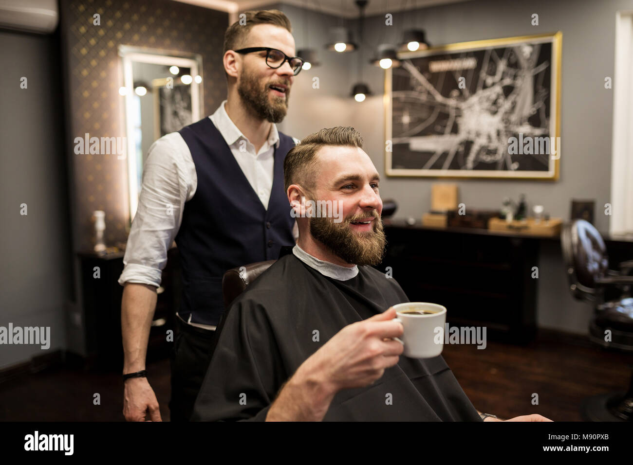 Portrait of happy barber and customer drinking coffee in salon - Stock Image