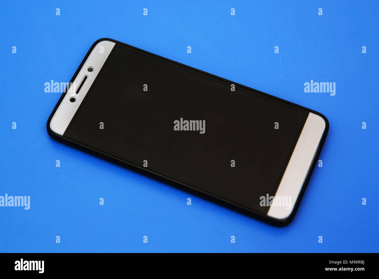 Black mobile smart phone mock up. This smartphone mock-up isolated on blue background. black smartphone with black screen. Android mobile phone . Can  Stock Photo