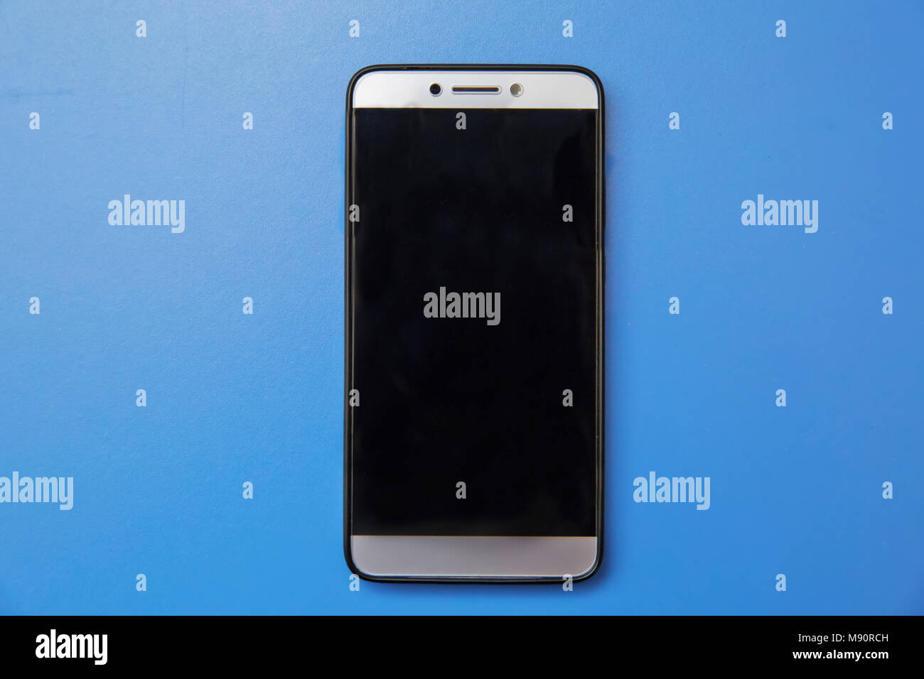 Black mobile smart phone mock up. This smartphone mock-up isolated on blue background. black smartphone with black screen. Android mobile phone . Can  Stock Photo