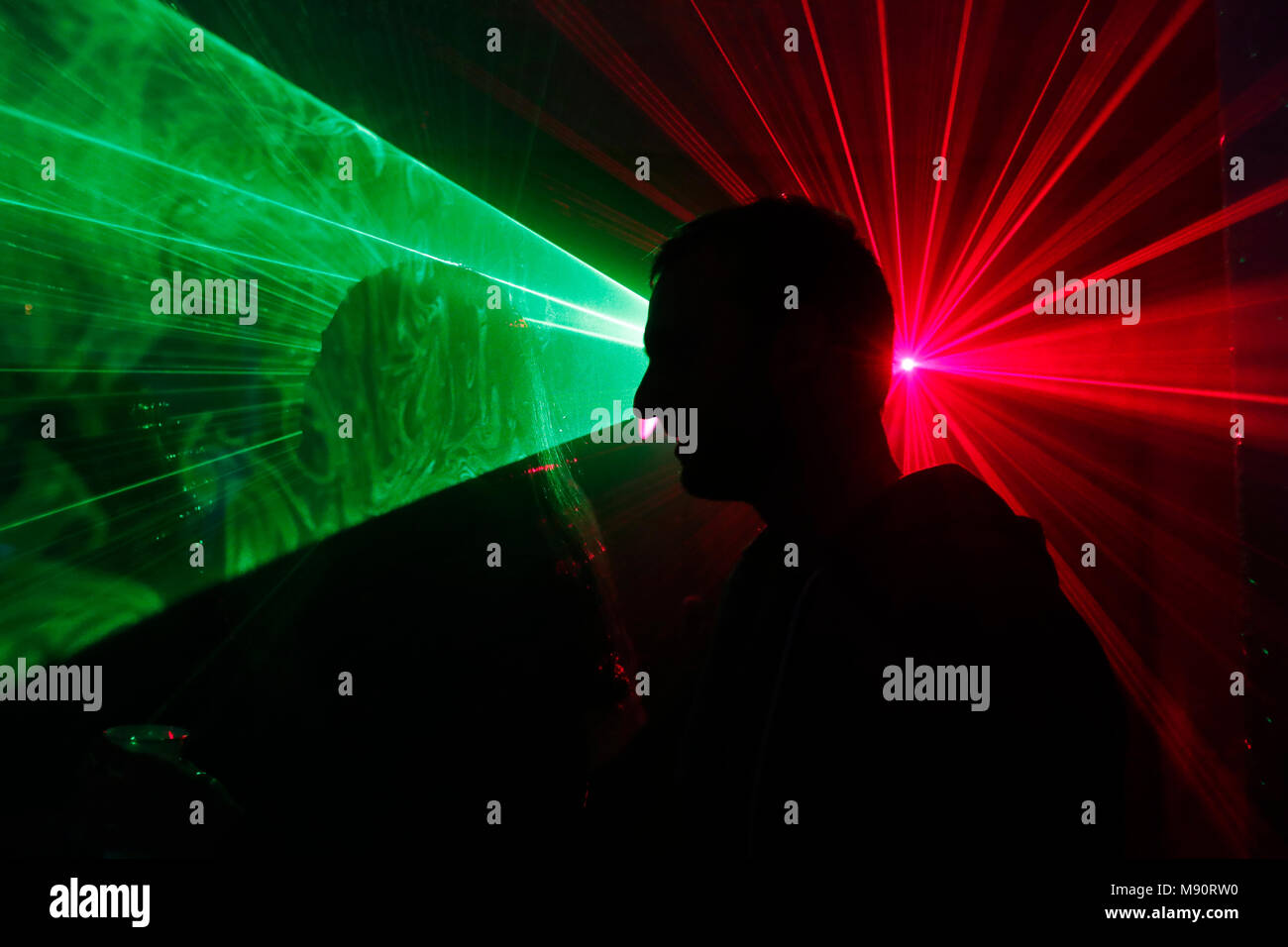 Silhouette of a man dancing at a disco with laser lights. - Stock Image