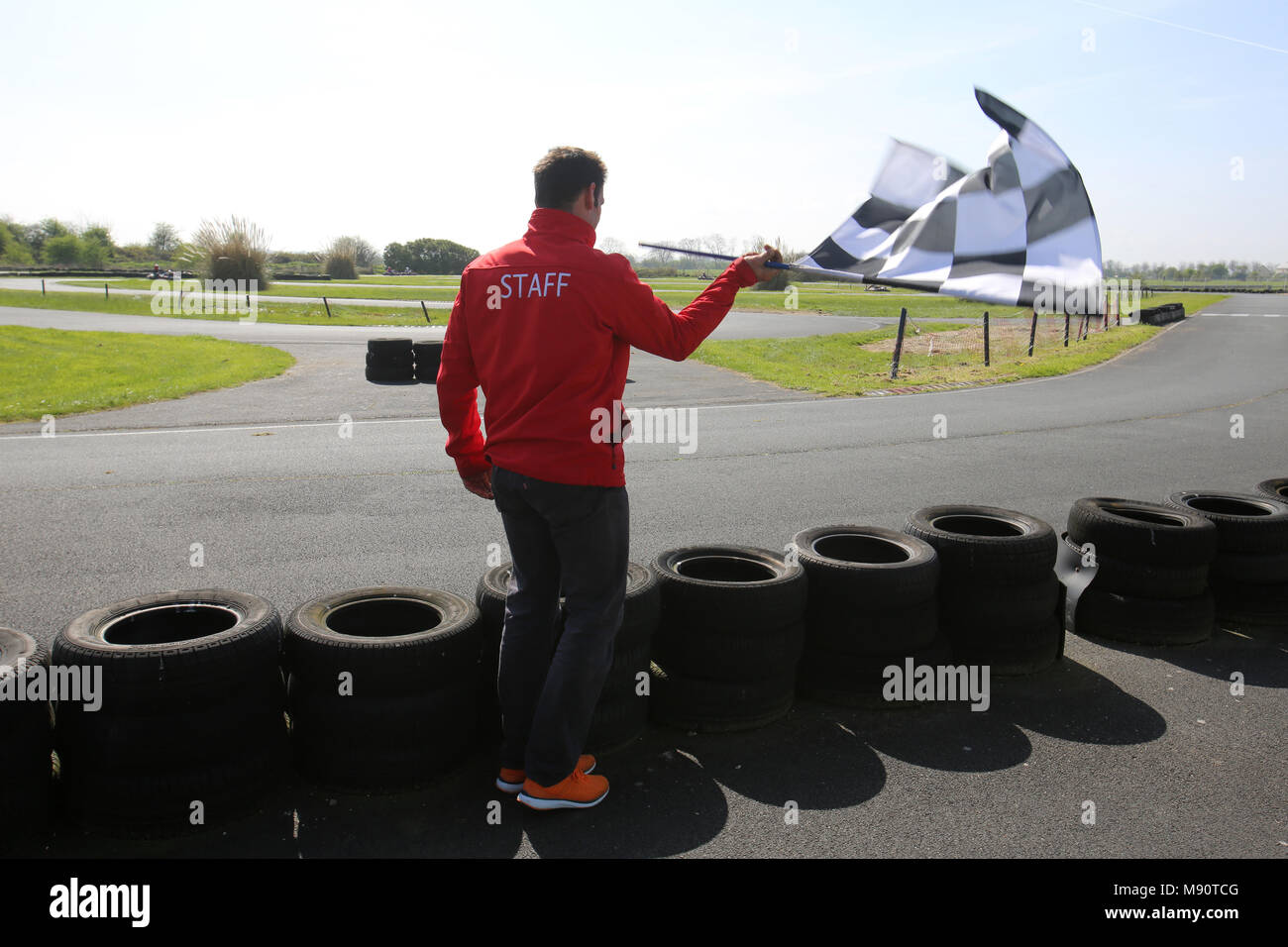 go kart track employee waving a finish flag cabourg france stock
