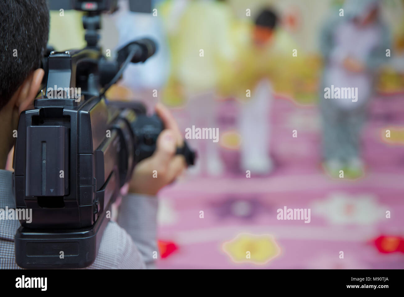 Professional Video camera operator working his equipment video, camera, media blurred background . - Stock Image