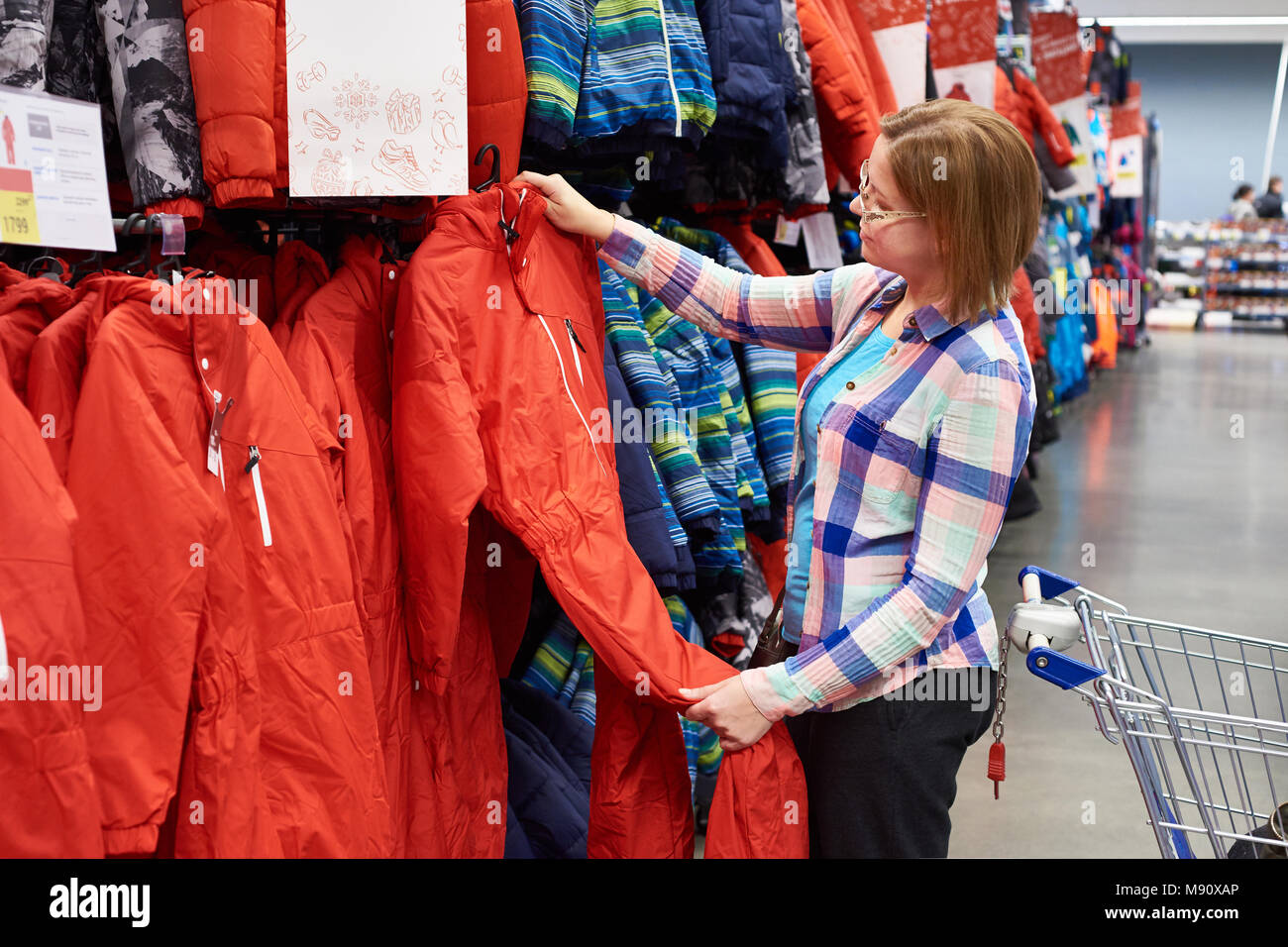 Woman chooses a ski jumpsuit in a sports store - Stock Image