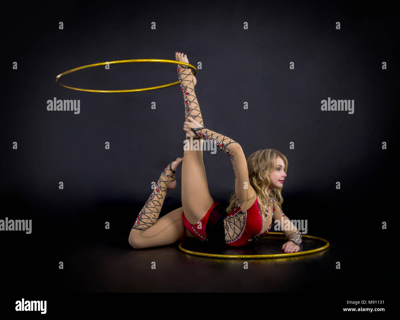 The contortionist girl in stage costume with hoops. Studio shot on dark background. - Stock Image