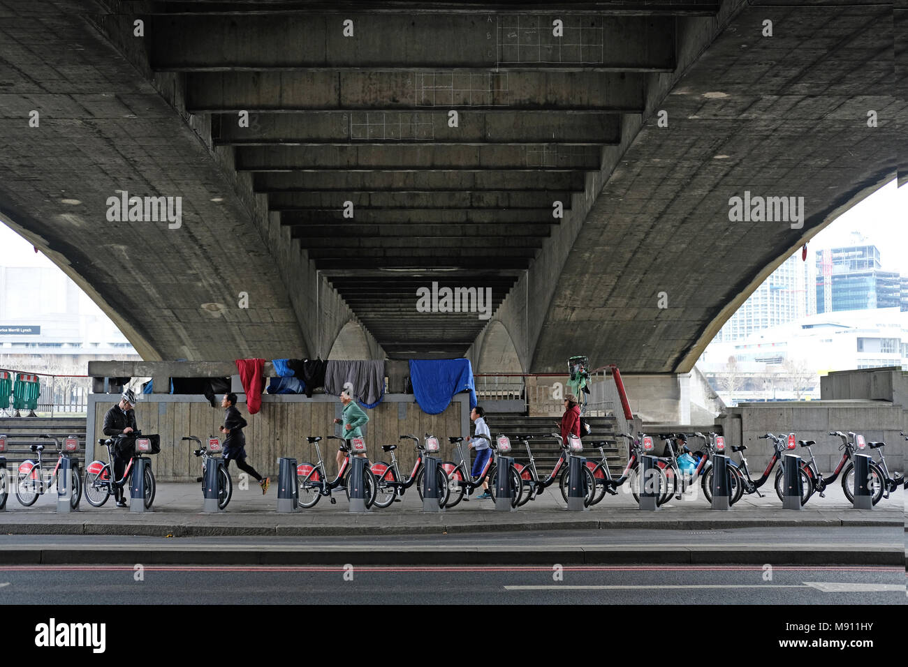 Runners under Waterloo Bridge in London. - Stock Image