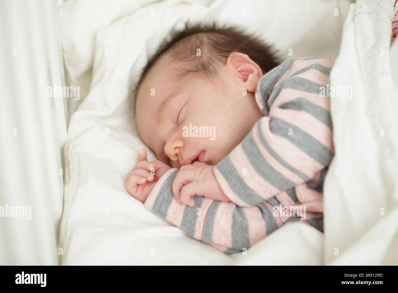 Small sleeping baby in bed (up to 20 days) - Stock Image