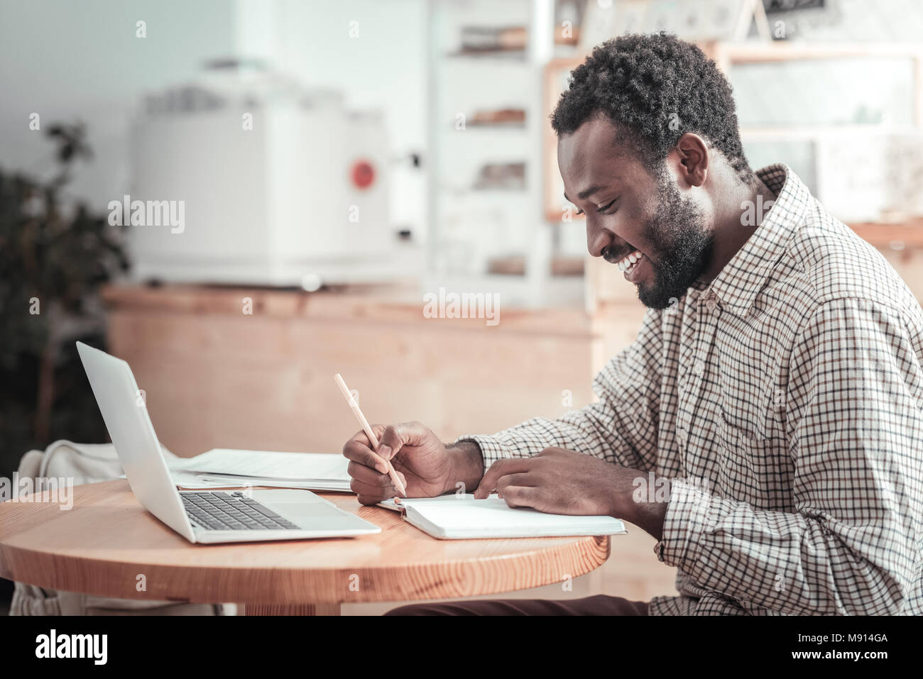 Happy delighted student reading his lectures - Stock Image