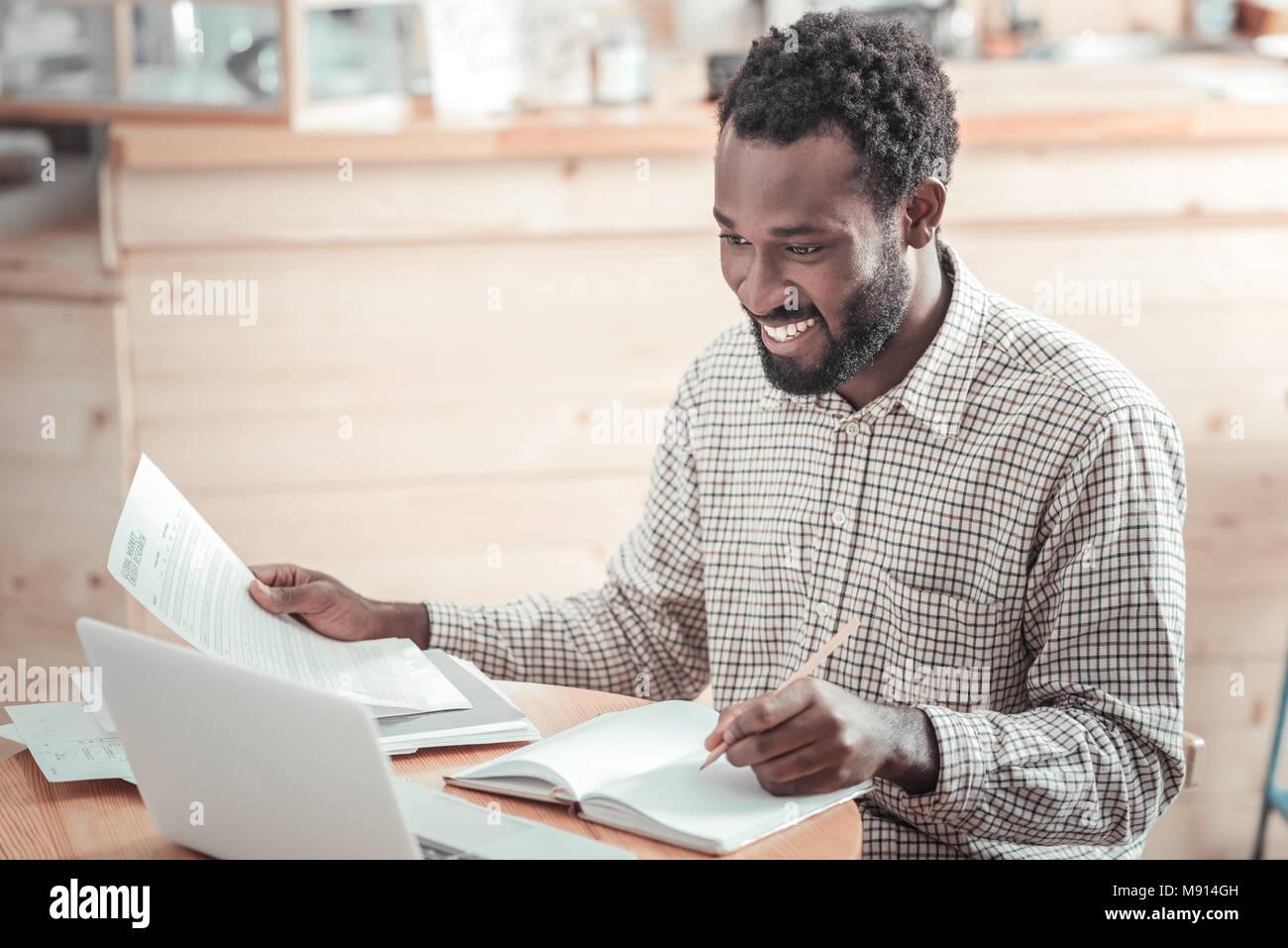 Joyful positive man preparing his home task - Stock Image