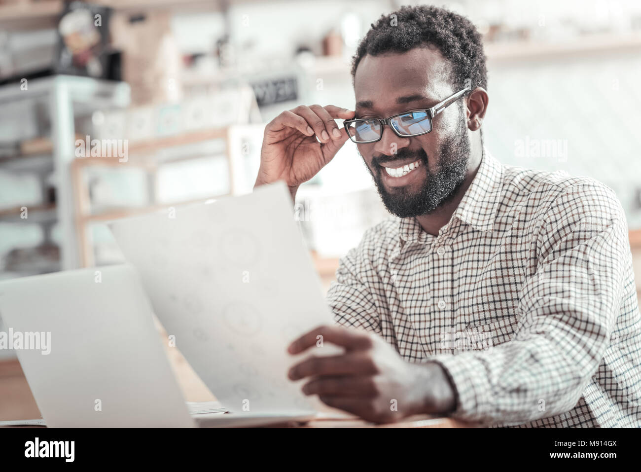 Cheerful nice man fixing his glasses - Stock Image