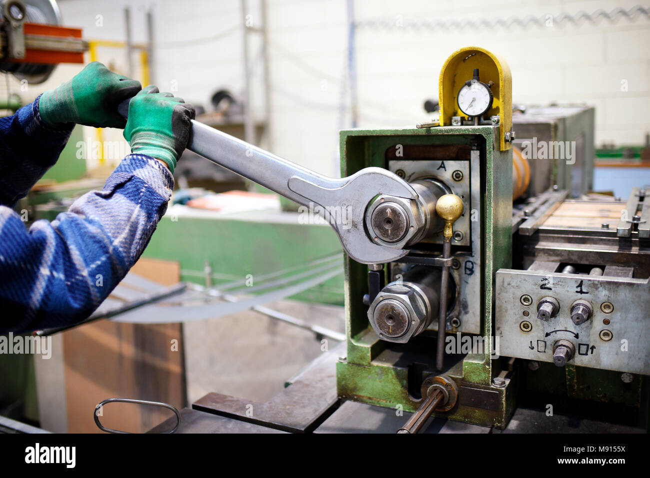 Worker adjusting machinery with large metal wrench - Stock Image