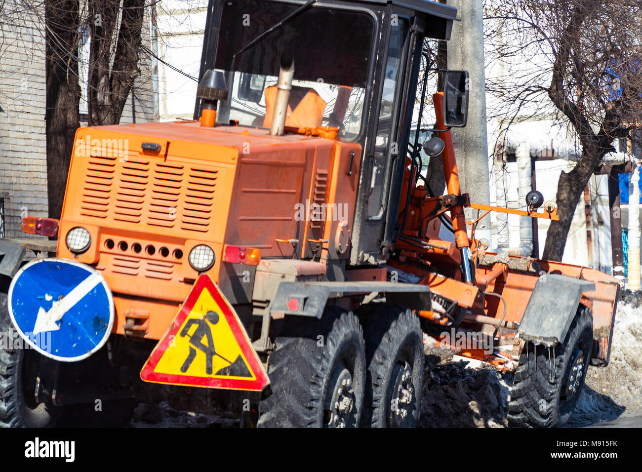 Tractor with snowplow on the street - Stock Image