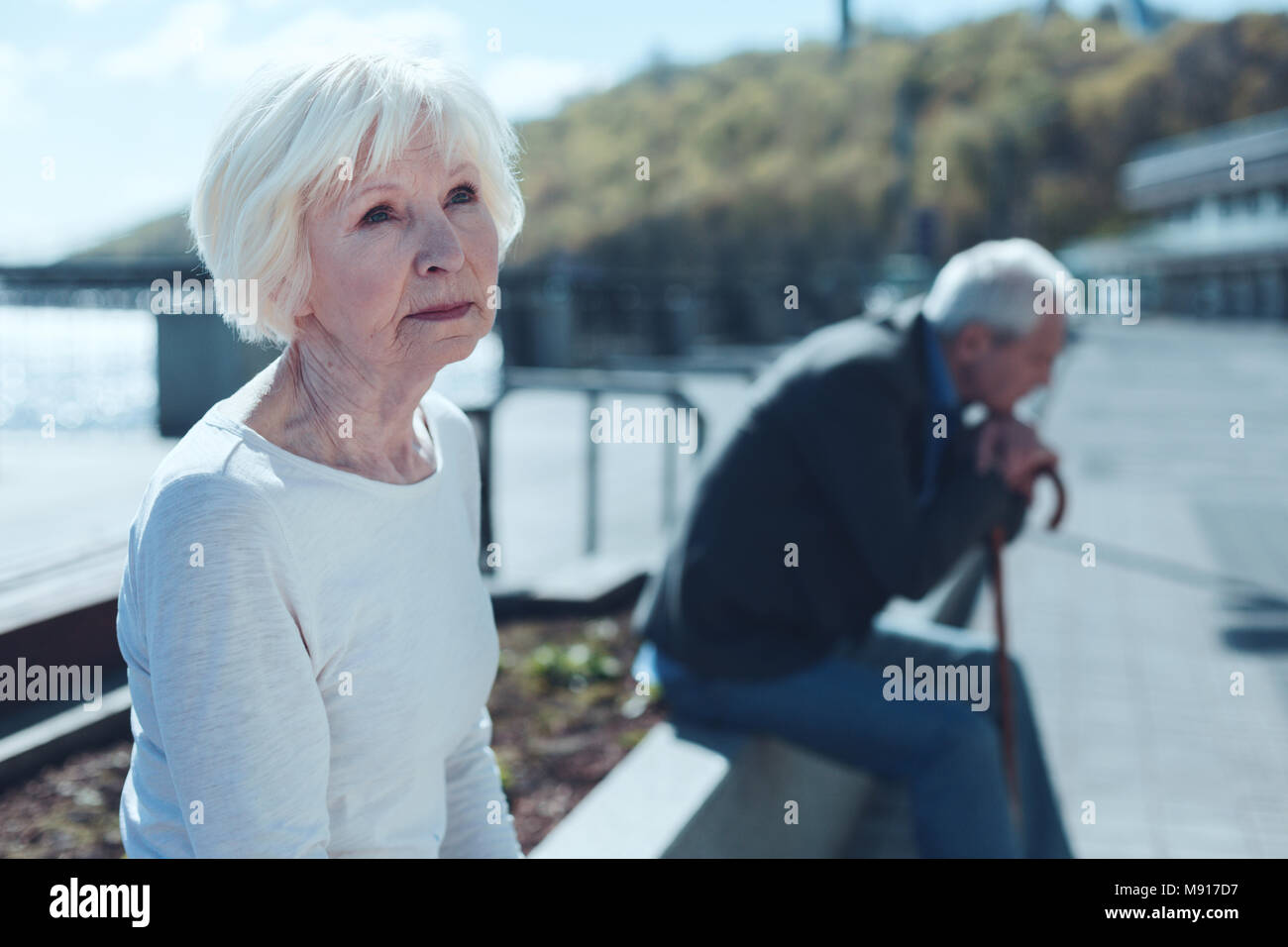 Beautiful retired woman thinking of her younger self - Stock Image