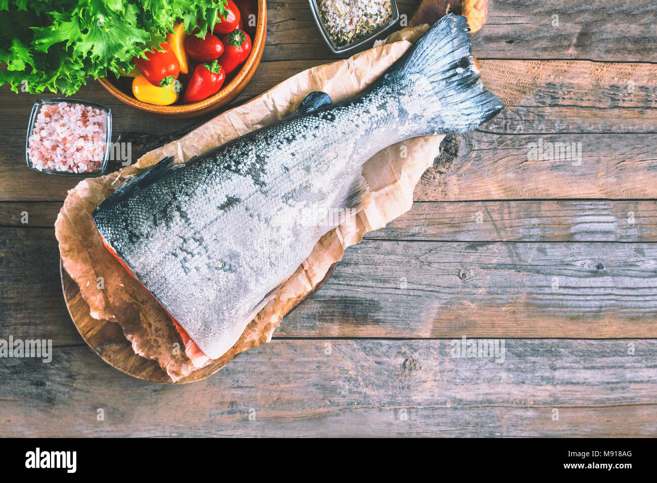 A large piece of salmon lying on a wooden table for cooking. Food anti-aging body. Copy the space. - Stock Image