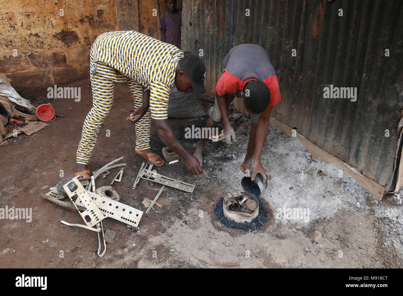 Smithy in Bohicon, Benin. Boss and young employee. - Stock Image
