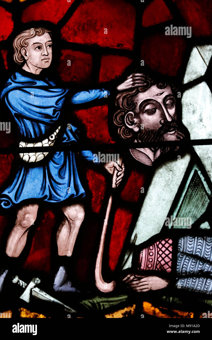 Saint-Pierre-le-Jeune Protestant Church. David hoists the severed head of Goliath.  Stained glass window.  Strasbourg. France. - Stock Image