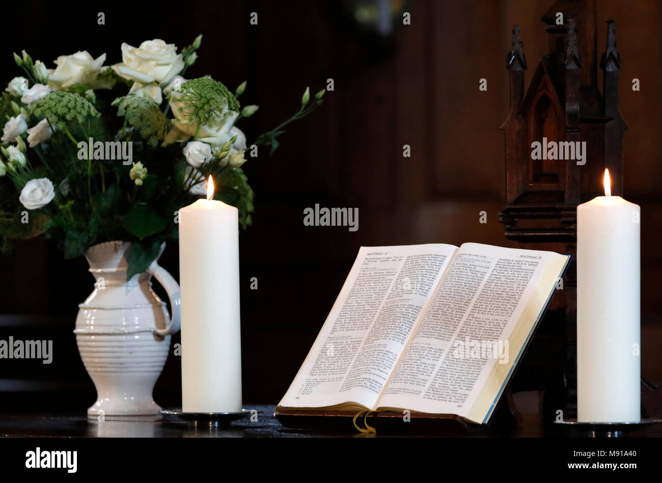 Church candles and open  bible on an altar.  Strasbourg. France. Stock Photo