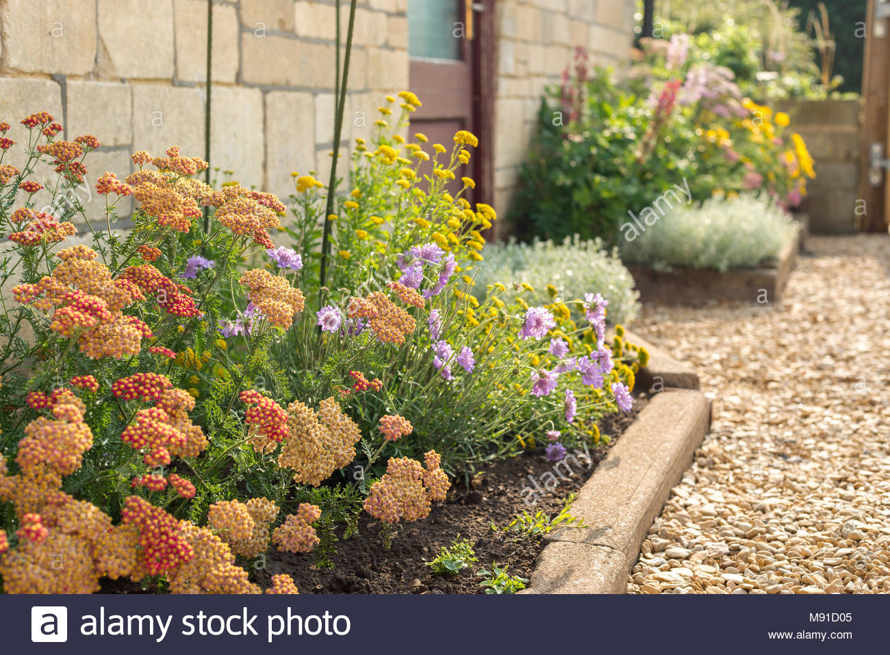 A Flower Border By The Side Of A Gravel Drive, In Front Of A House