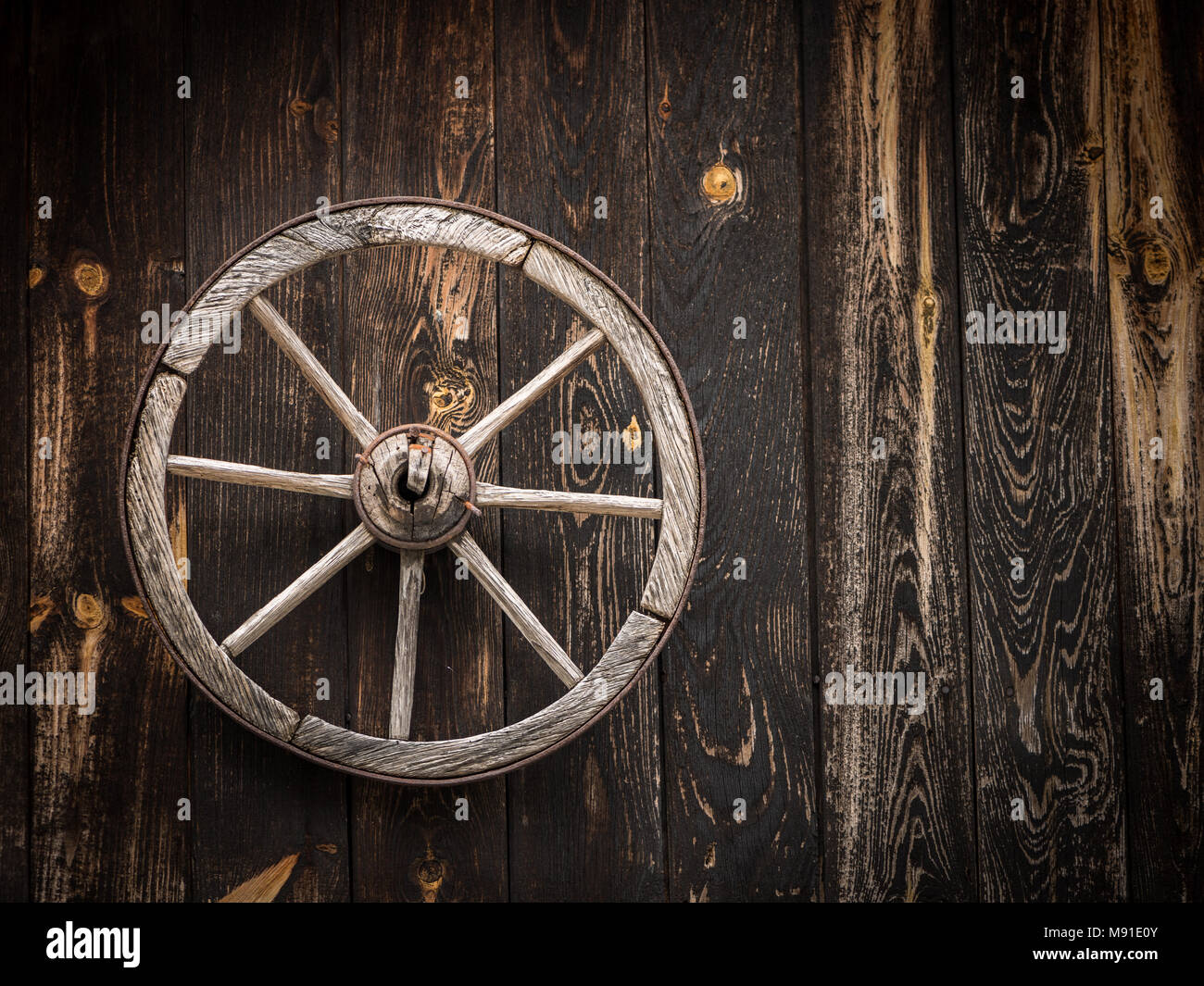 Old cartwheel hanging on a wooden barn wall, Austria - Stock Image