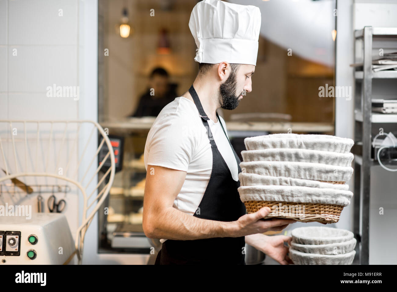 Baker with baking forms at the bakery - Stock Image