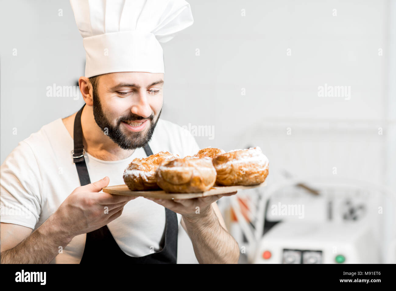 Confectioner with sweet pastry indoors - Stock Image